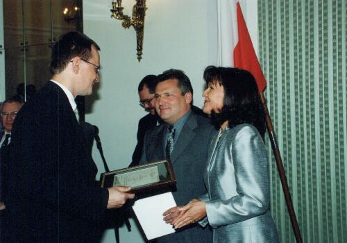 Prezydent Aleksander Kwaśniewski wręcza dyrektorowi firmy list gratulacyjny od Stowarzyszenia Porozumienie Bez Barier